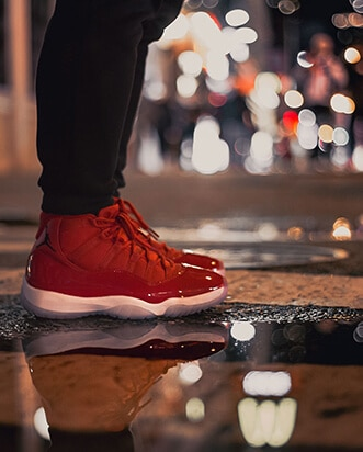 An Instagram post image of a below the knee shot of a man in red trainers standing on the road at night just after rain.
